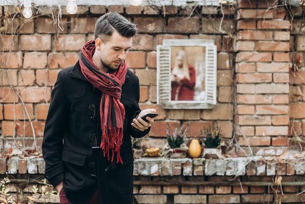 Homme caucasien solitaire debout dans la rue et regardant son smartphone en attendant sa petite amie. notion de date. fille à l'arrière-plan. stock photo