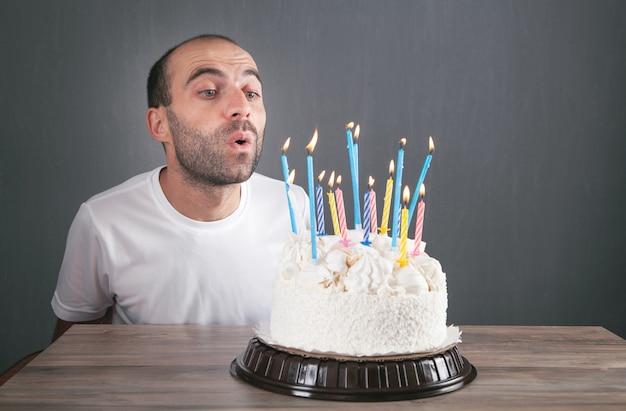 Homme caucasien soufflant des bougies d'anniversaire.