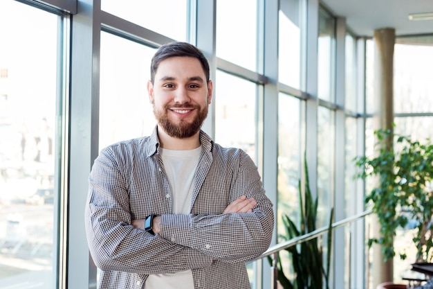 Homme caucasien souriant, debout près d'une fenêtre pleine longueur au bureau seul. jeune homme barbu heureux et réussi, les bras croisés. bel homme d'affaires intelligent en chemise décontractée. freelance dans un espace de coworking.