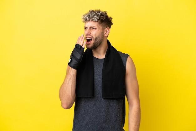 Homme caucasien sport isolé sur fond jaune bâillant et couvrant la bouche grande ouverte avec la main