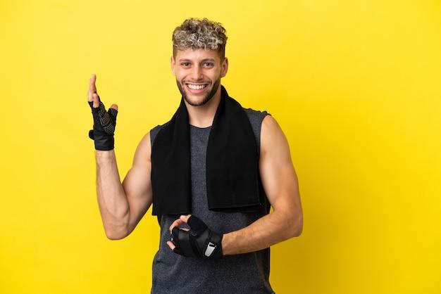 Homme caucasien sport isolé sur fond jaune faisant un geste de guitare