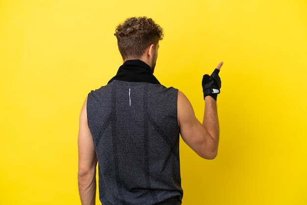 Homme caucasien sport isolé sur fond jaune pointant vers l'arrière avec l'index