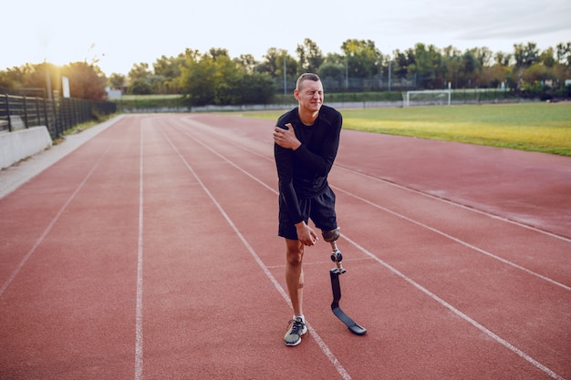 Homme caucasien sportif avec jambe artificielle debout sur une piste de course et tenant un bras douloureux.