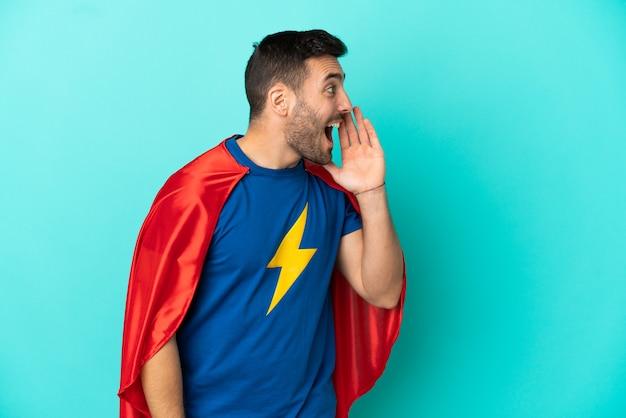Homme caucasien de super héros isolé sur fond bleu criant avec la bouche grande ouverte sur le côté