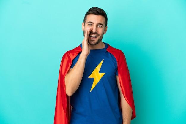 Homme caucasien de super héros isolé sur fond bleu criant avec la bouche grande ouverte