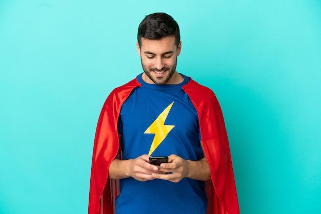 Homme caucasien de super héros isolé sur fond bleu envoyant un message avec le mobile