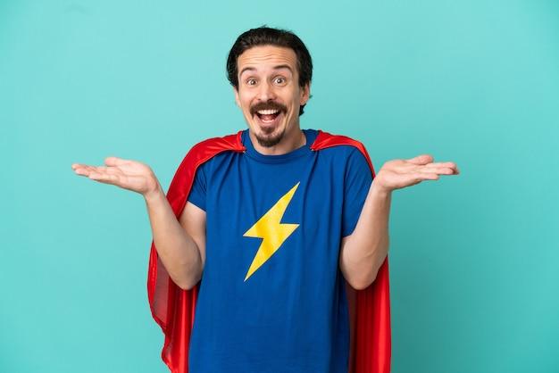 Homme caucasien de super héros isolé sur fond bleu avec une expression faciale choquée