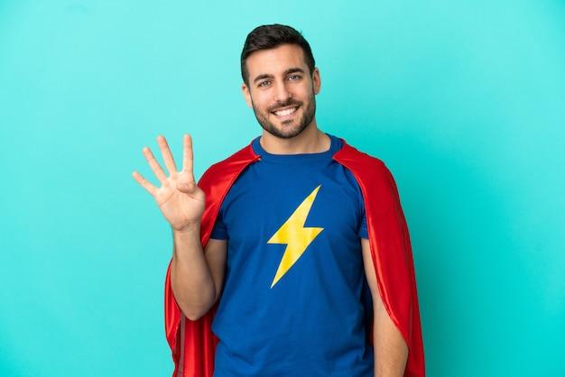 Homme caucasien de super héros isolé sur fond bleu heureux et comptant quatre avec les doigts