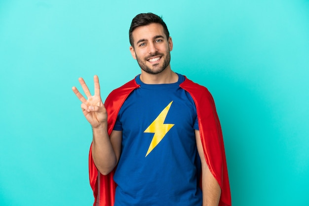 Homme caucasien de super héros isolé sur fond bleu heureux et comptant trois avec les doigts