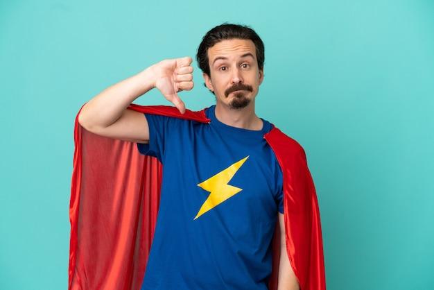 Homme caucasien de super héros isolé sur fond bleu montrant le pouce vers le bas avec une expression négative