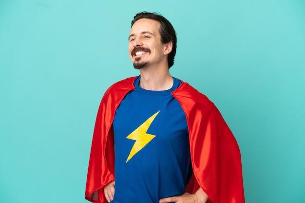 Homme caucasien de super héros isolé sur fond bleu posant avec les bras à la hanche et souriant