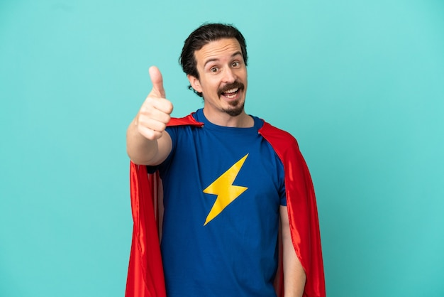 Homme caucasien de super héros isolé sur fond bleu avec le pouce levé parce que quelque chose de bien s'est produit