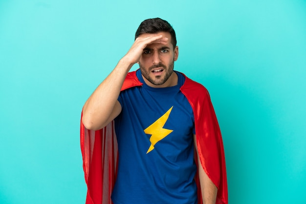 Homme caucasien de super héros isolé sur fond bleu regardant loin avec la main pour regarder quelque chose