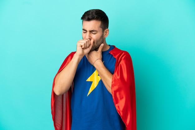 Un homme caucasien de super héros isolé sur fond bleu souffre de toux et se sent mal