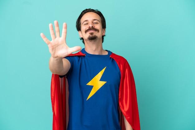 Homme caucasien de super héros d'isolement sur le fond bleu comptant cinq avec des doigts
