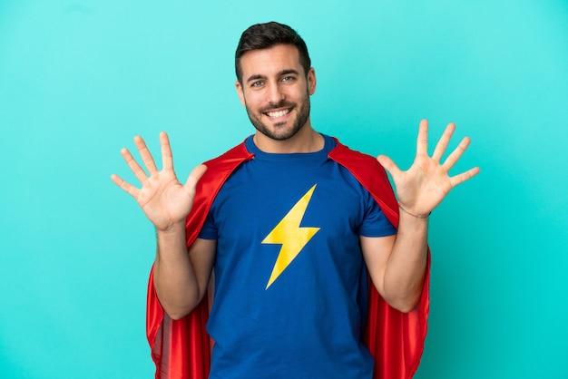 Homme caucasien de super héros d'isolement sur le fond bleu comptant dix avec des doigts
