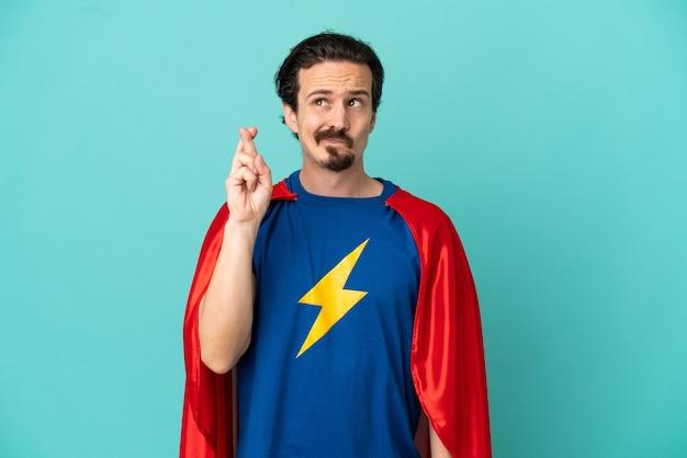 Homme caucasien de super héros d'isolement sur le fond bleu avec des doigts croisés et souhaitant le meilleur