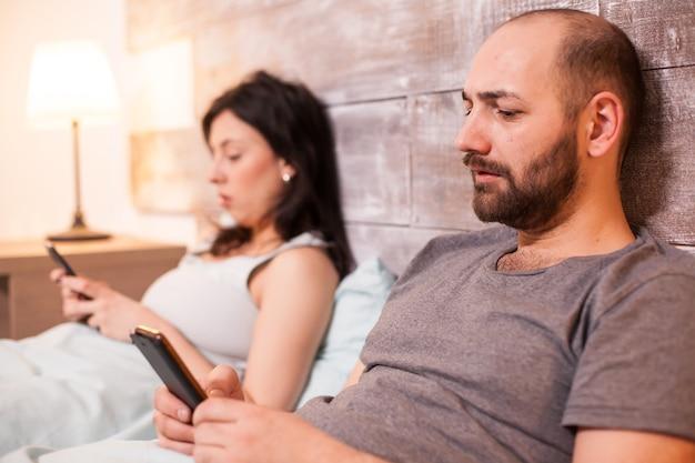 Homme caucasien surfant sur internet en utilisant son téléphone avant de se coucher et ayant une communication avec sa femme.