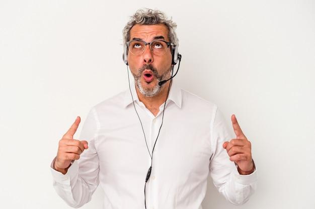 Homme caucasien de télévendeur d'âge moyen isolé sur fond blanc pointant vers le haut avec la bouche ouverte.