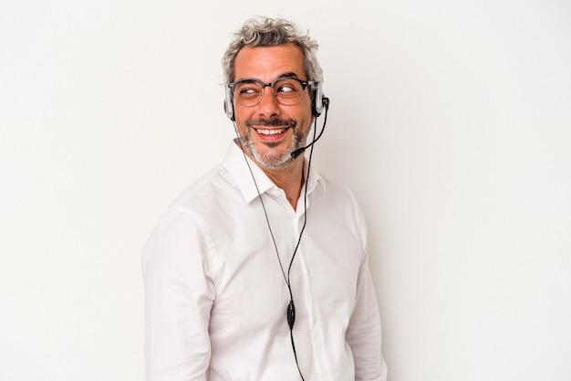 L'homme caucasien de télévendeur d'âge moyen isolé sur fond blanc regarde de côté souriant, gai et agréable.