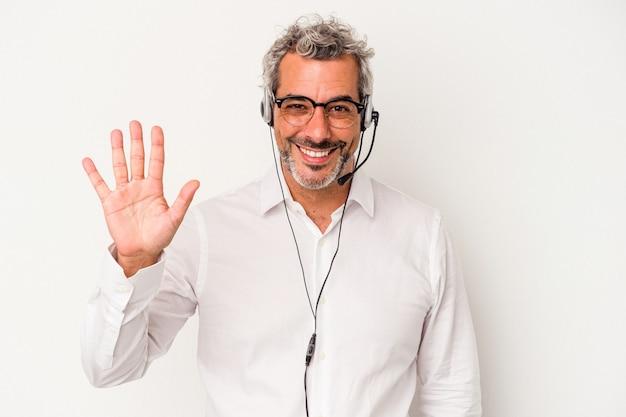 Homme caucasien de télévendeur d'âge moyen isolé sur fond blanc souriant joyeux montrant le numéro cinq avec les doigts.