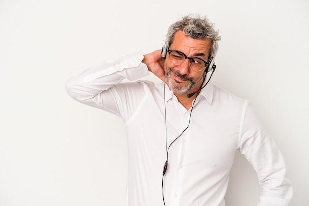Homme caucasien de télévendeur d'âge moyen isolé sur fond blanc touchant l'arrière de la tête, pensant et faisant un choix.