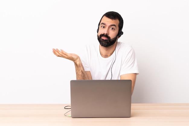 Homme caucasien de télévendeur travaillant avec un casque et avec un ordinateur portable ayant des doutes.