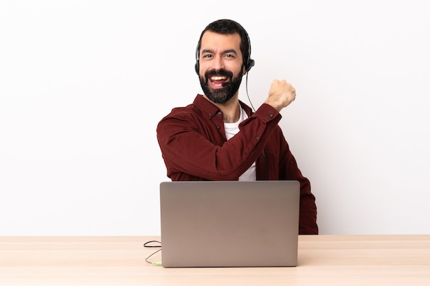 Homme caucasien de télévendeur travaillant avec un casque et avec un ordinateur portable célébrant une victoire.