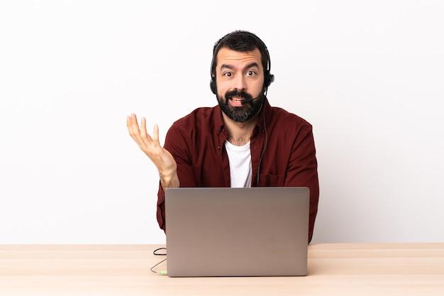 Homme caucasien de télévendeur travaillant avec un casque et avec un ordinateur portable faisant le geste de doutes.