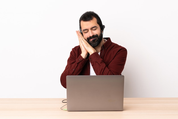 Homme caucasien de télévendeur travaillant avec un casque et avec un ordinateur portable faisant le geste de sommeil dans une expression dorable.