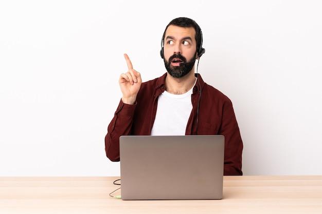 Homme caucasien de télévendeur travaillant avec un casque et avec un ordinateur portable en pensant à une idée pointant le doigt vers le haut.