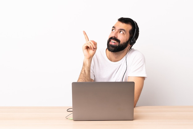 Homme caucasien de télévendeur travaillant avec un casque et avec un ordinateur portable pointant vers le haut une excellente idée.
