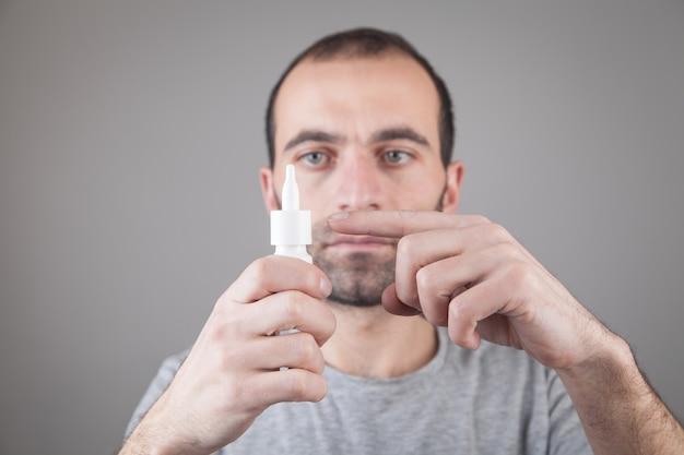 Homme caucasien tenant une bouteille de gouttes pour les yeux.