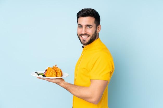 Homme caucasien, tenue, gaufres, isolé, sur, mur bleu, sourire, beaucoup