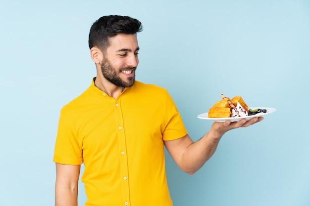 Homme caucasien, tenue, gaufres, sur, mur bleu, à, expression heureuse