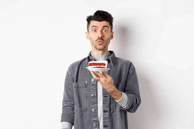 Homme célébrant son anniversaire, soufflant une bougie sur un gâteau et faisant un souhait, debout sur fond blanc.