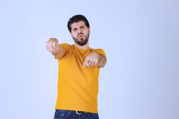 Homme de célébrité pointant et parlant à quelqu'un de ses spectateurs.