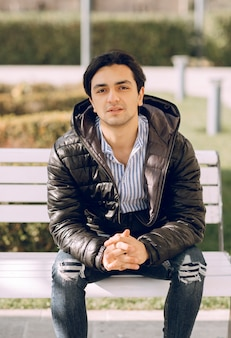 Homme célibataire assis sur le banc dans le parc et pensant. photo de haute qualité
