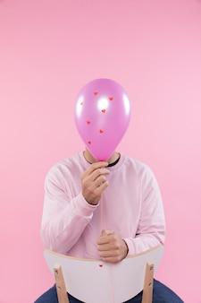 Homme sur une chaise tenant un ballon violet