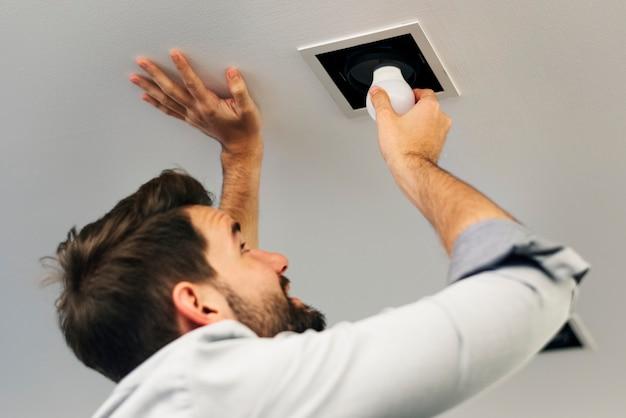 Homme changeant une ampoule