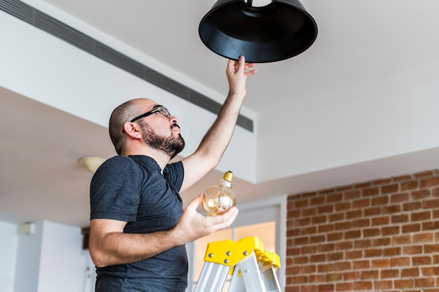 Homme changeant l'ampoule