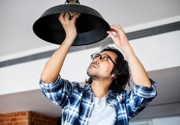 Homme changeant d'ampoule