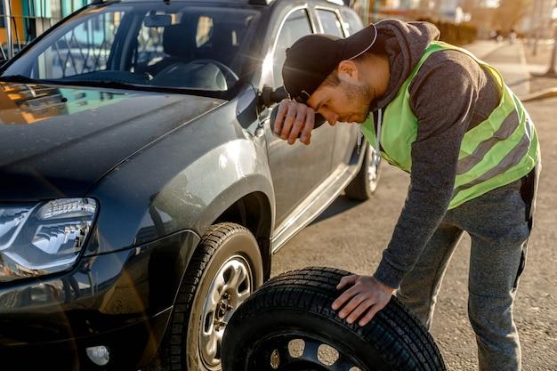 Homme changeant de roue après une panne de voiture.