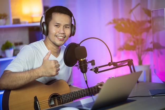 Homme chantant avec un casque et jouant de la guitare enregistrant une nouvelle chanson avec microphone dans le studio d'enregistrement à domicile