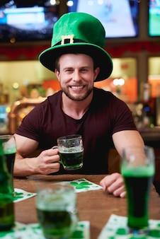 Homme avec chapeau de lutin et bière célébrant la saint patrick