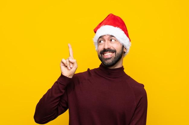 L'homme avec un chapeau de noël sur fond jaune isolé à l'intention réalise la solution tout en soulevant un doigt vers le haut