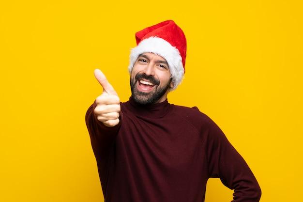 Homme avec un chapeau de noël sur fond jaune isolé avec le pouce levé parce que quelque chose de bien est arrivé