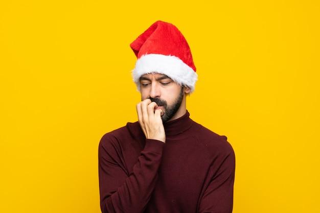 Homme avec chapeau de noël sur mur jaune isolé ayant des doutes