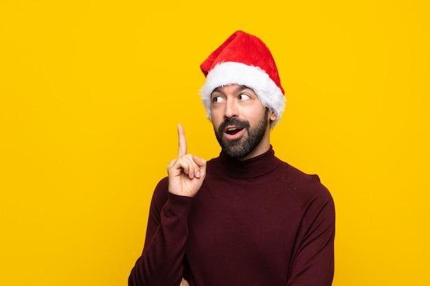 Homme avec un chapeau de noël sur un mur jaune isolé, pensant une idée pointant le doigt vers le haut