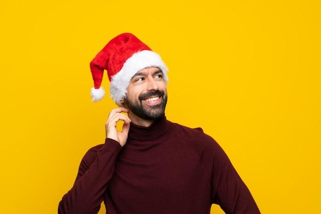 Homme avec un chapeau de noël sur un mur jaune isolé, pensant une idée